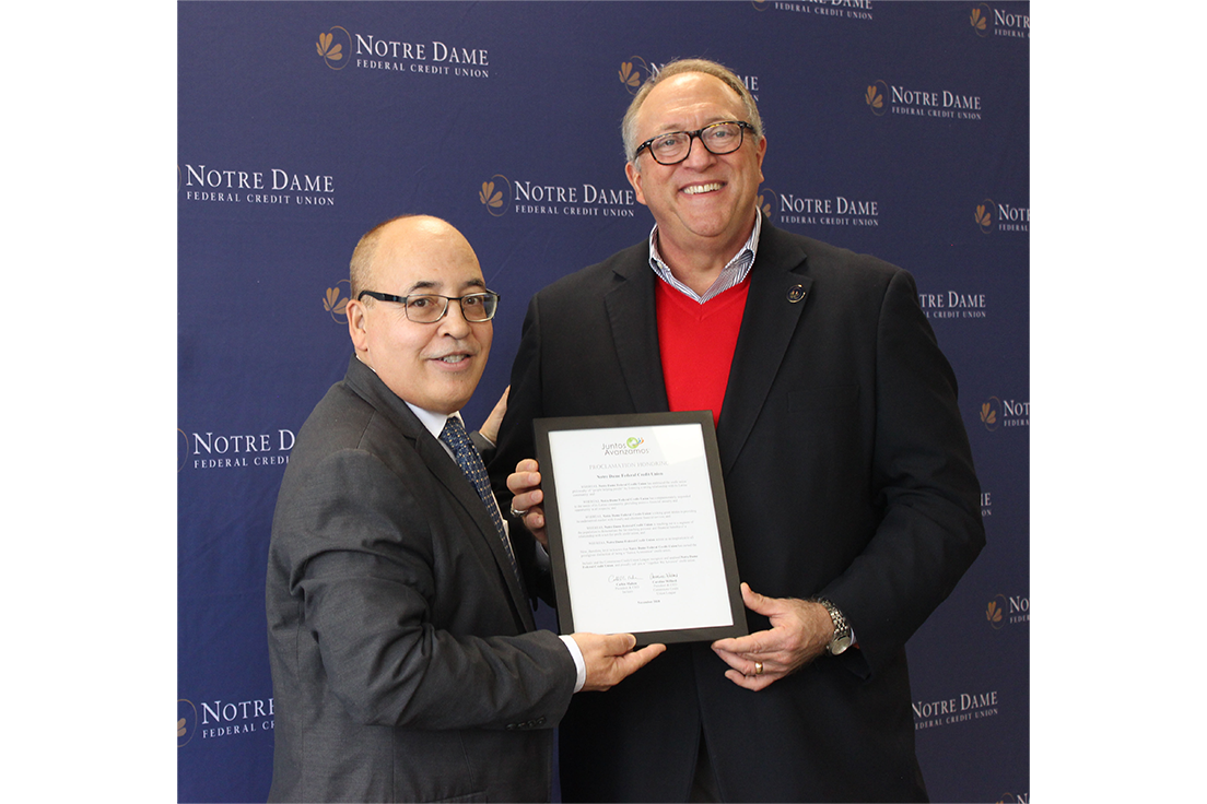 Pablo DeFilippi of Inclusiv presents Notre Dame FCU President and CEO Tom Gryp with the Juntos Avanzamos proclamation